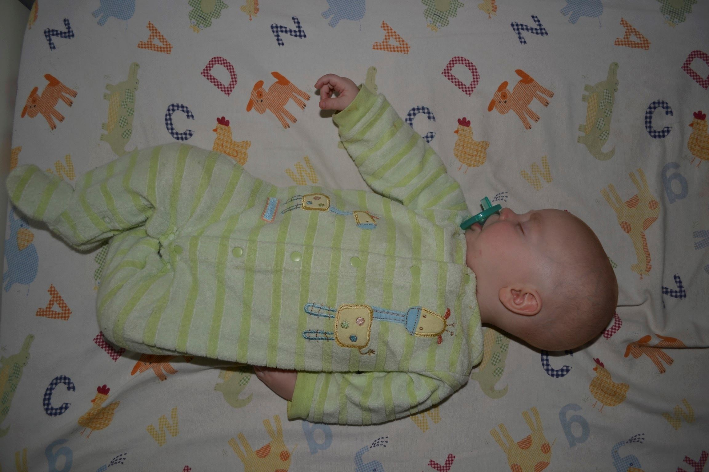 Image from above of infant sleeping on back in crib