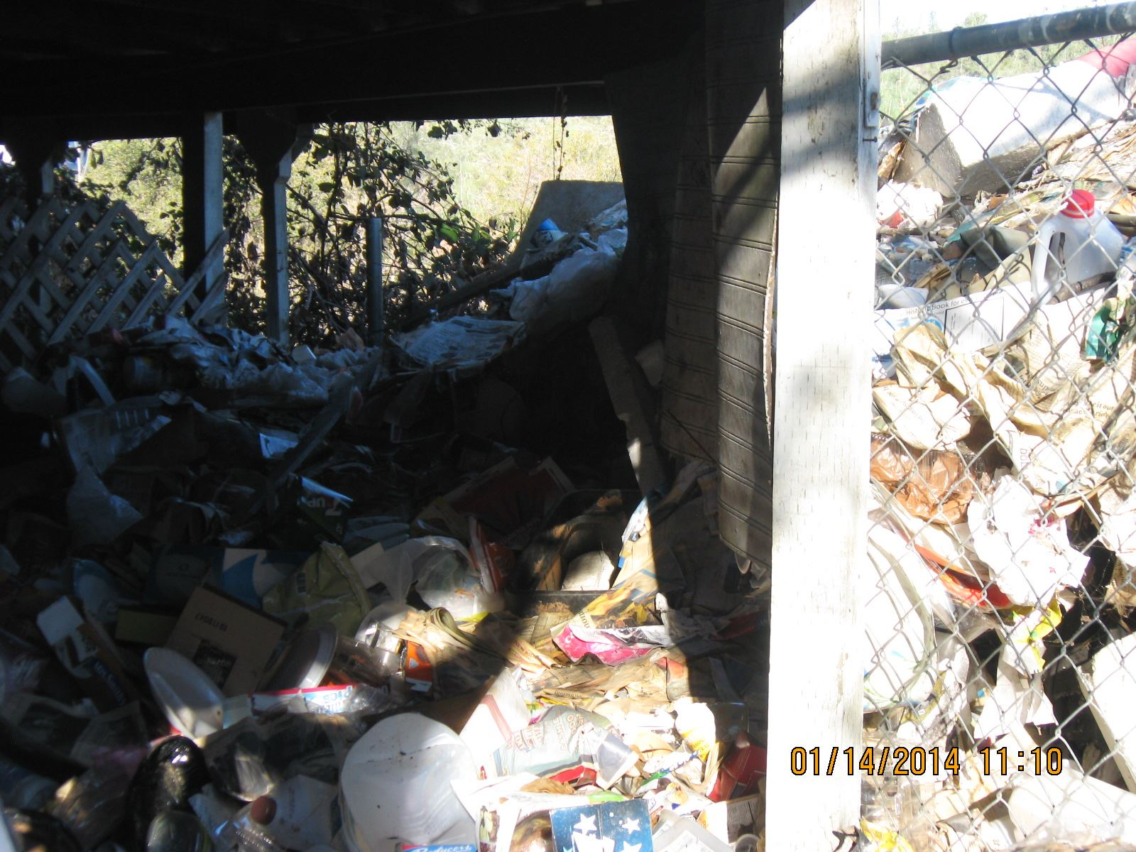 A pile of garbage piled up next to a house.